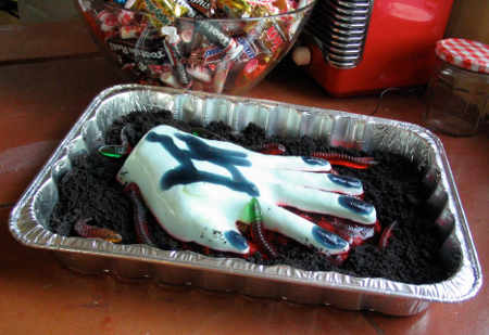 Hand of Glory on a bed of chocolate crumb dirt being crawled over by gummy worms
