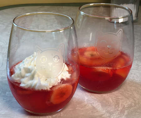 strawberry Jell-O with peach and banana slices in two stemless wine glasses