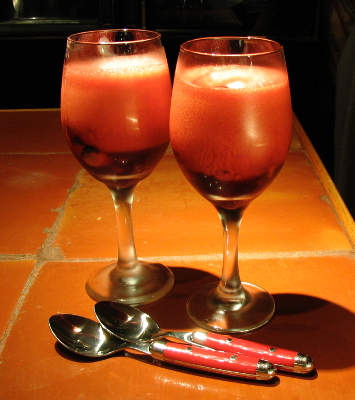 Two wine glasses of some sort of dark red fruity stuff with a lot of foam on top