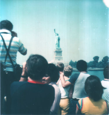 ferry passengers in the foreground, the Statue of Liberty looming in the distance