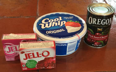 two boxes of cherry Jell-O, a tub of Cool Whip, and a can of cherries