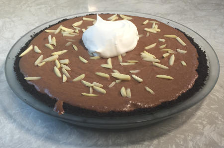 chocolate creme pie garnished with slivered almonds and a Cool Whip dollop