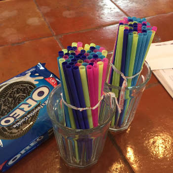 two glasses with bundles of straws, next to a package or Oreos