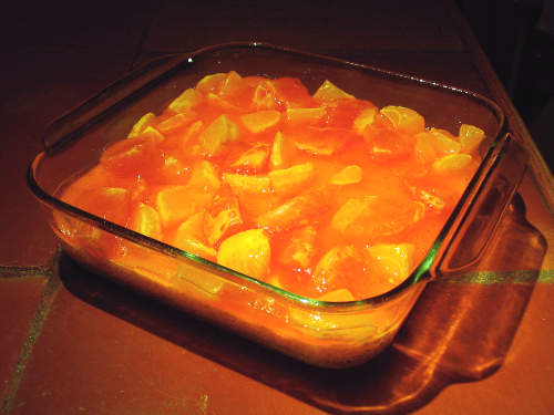 square baking pan containing a combination of orange Jell-O and orange and grapefruit sections