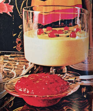 trifle bowl of Jell-O dish topped with maraschion cherries, with smaller bowl of violently-colored sauce in front