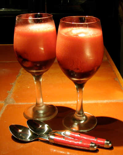 two red wine glasses containing a frothy cherry gelatin dessert