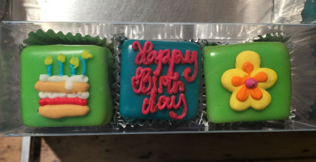 three small square decorated cakes