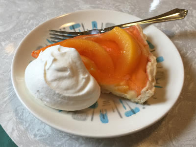 slice of Peach Gem Tart with a dollop of whipped cream