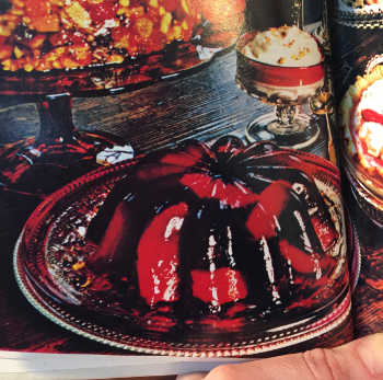 photo from book of Jell-O mold containing orange sections, and a small dish of whipped topping, on a buffet table