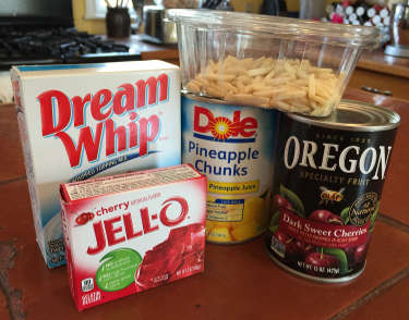 Dream Whip, cherry Jell-O, slivered almonds, pineapple chunks, sweet dark cherries