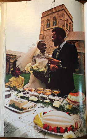 flower girl, bride and groom standing next to a table laden with Jell-O dishes