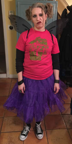 Your Humble Narrator, with t-shirt, purple tutu skirt, black Chucks, black wings, heavy eye makesup, and a sneer